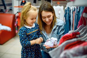 Mother and little baby buying clothes, kid's store