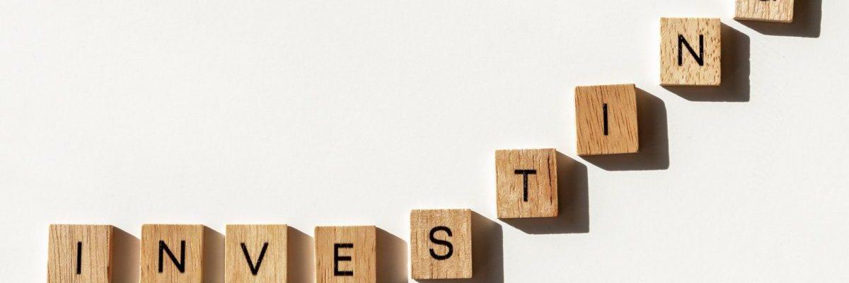 Investing letter tiles on white